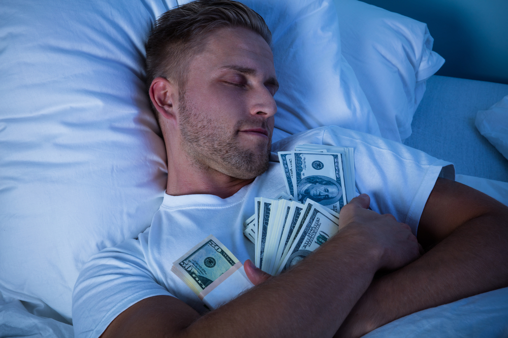 Man Sleeping On Bed With Bundle Of Currency Notes